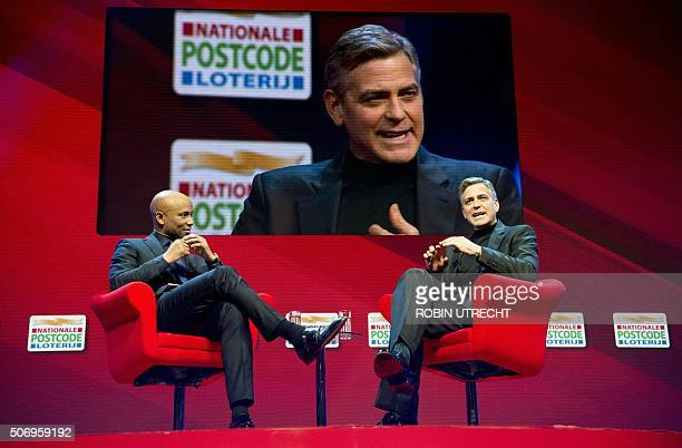 Dutch host Humberto Tan listens to US actor George Clooney during the Goed Geld Gala charity event at the Carre Theatre in Amsterdam on January 26...