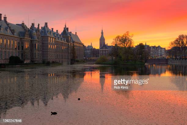 dutch houses of parliament ( binnenhof ) and church reflected in the court pond ( hofvijver ) at sunset - la haya fotografías e imágenes de stock
