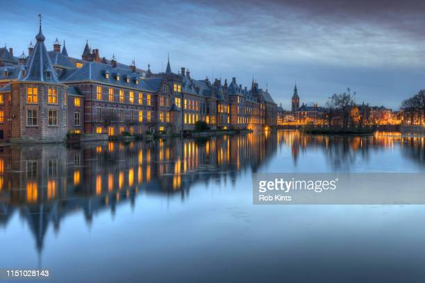 dutch houses of parliament ( het torentje and binnenhof ) in den haag reflected in the court pond ( hofvijver ) after sunset - binnenhof stock photos and pictures