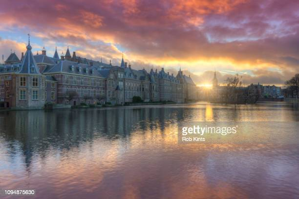 dutch houses of parliament ( het torentje and binnenhof ) reflected in the court pond ( hofvijver ) at sunset - binnenhof stock photos and pictures