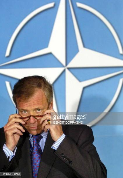 Dutch Jaap de Hoop Scheffer puts his glasses on during his first press conference as NATO Secretary General, 05 January 2004 at the NATO headquarters...