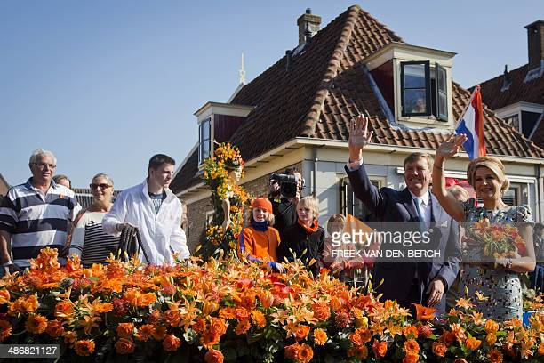 Dutch King Willem-Alexander and his wife Queen Maxima wave to fans during a boat trip in De Rijp, on April 26 as part of the first King's Day , the...