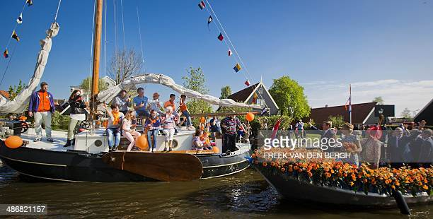 Dutch King Willem-Alexander and his wife Queen Maxima wave to the crowd during a boat trip in De Rijp, on April 26 as part of the first King's Day ,...