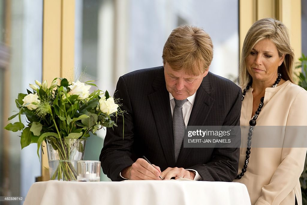 Dutch King Willem-Alexander and Queen Maxima sign a condolence register at the Ministry of Safety and Justice in The Hague, the Netherlands, on July 18, 2014, in meory of the victims of Malaysia Airlines flight MH17 that crashed in eastern Ukraine on July 17 on a flight from Amsterdam to Kuala Lumpur. A team of international monitors arrived on July 18 at the site in rebel-held eastern Ukraine where the jet crashed with 298 people on board after apparently being downed by a surface-to-air missile.