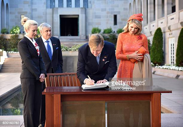 Dutch King WillemAlexander and Queen Maxima sign the visitors book during a visit to the Australian War Memorial in Canberra on November 2 2016 The...