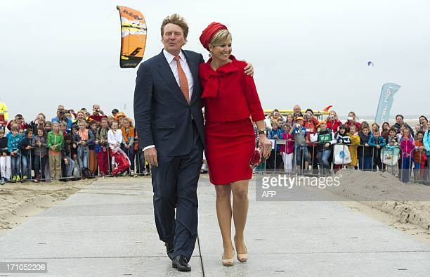 Dutch King WillemAlexander and Queen Maxima walk on the beach during their visit to Brouwersdam SouthHolland on June 21 2013 The royal couple ended...