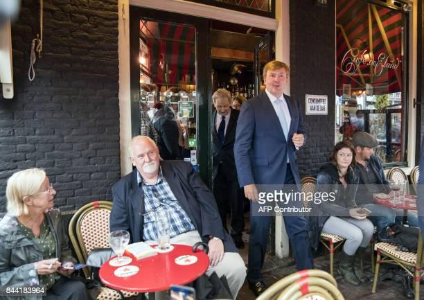 """Dutch King Willem-Alexander leaves a cafe following by Amsterdam's mayor Eberhard van der Laan, as he visits the Amsterdam neighborhood the """"Jordaan""""..."""