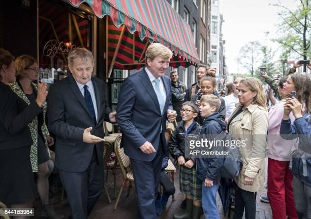 Dutch King Willem-Alexander leaves a cafe following by Amsterdam's mayor Eberhard van der Laan , as he visits the Amsterdam neighborhood the...