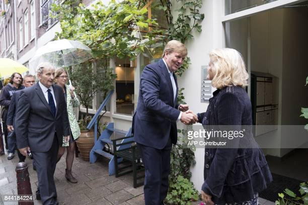 """Dutch King Willem-Alexander shakes hands with a resident, as he visits the Amsterdam neighborhood the """"Jordaan"""" flanked by Amsterdam's mayor Eberhard..."""