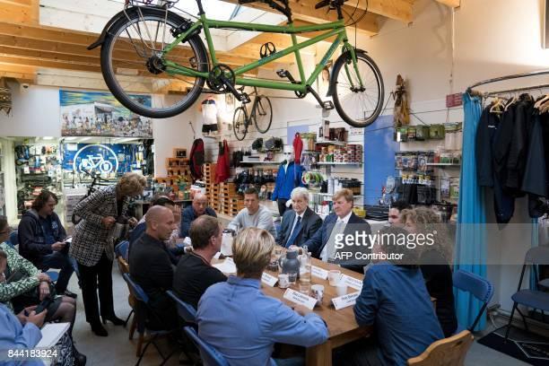 """Dutch King Willem-Alexander sits with Amsterdam's mayor Eberhard van der Laan , as he visits the Amsterdam neighborhood the """"Jordaan"""" in Amsterdam,..."""