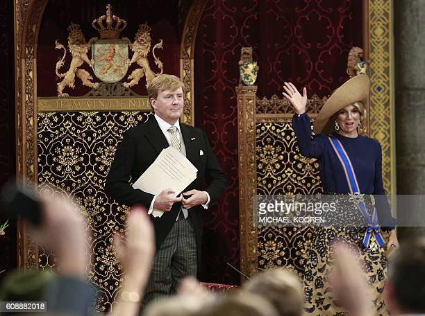Dutch King WillemAlexander stands after delivering a speech from the throne next to Queen Maxima waving in the Ridderzaal during the 'Prinsjesdag' in...