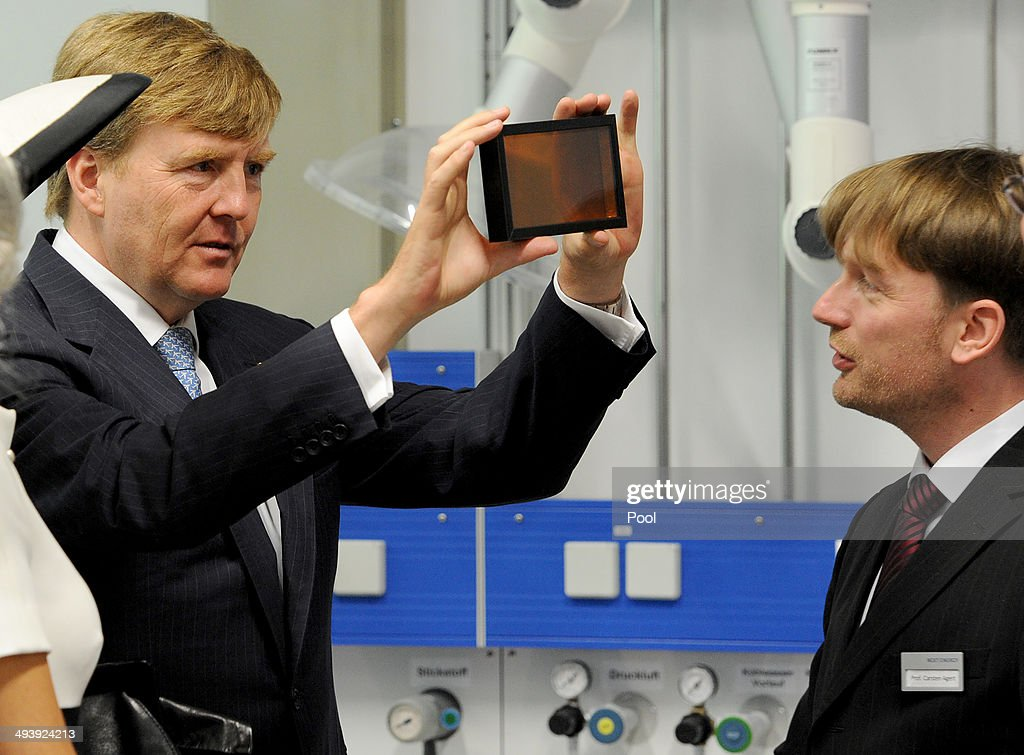 Dutch King Willem-Alexander talks to the institute's director Carsten Agert during their visit of the EWE research center's laboratory 'Next Energy' on May 26, 2014 in Oldenburg, Germany.