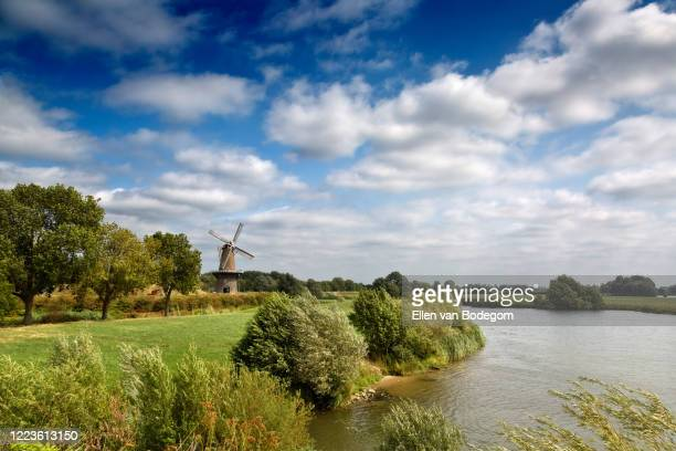 dutch landscape with view on windmill and river in summer - 干拓地 ストックフォトと画像