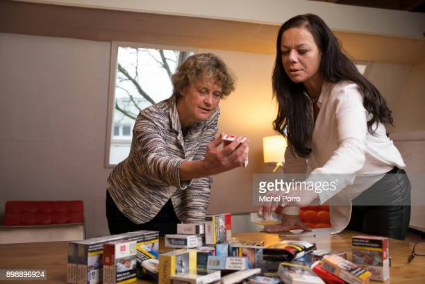Dutch lung cancer patient Anne Marie van Veen and her criminal lawyer Benedicte Ficq look at packets of cigarettes in preparation of the first ever...