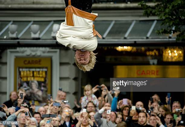 Dutch magician Hans Klok escapes from a straitjacket on July 10 2013 above the Amstel river in front of Carre Theater in Amsterdam The performance is...