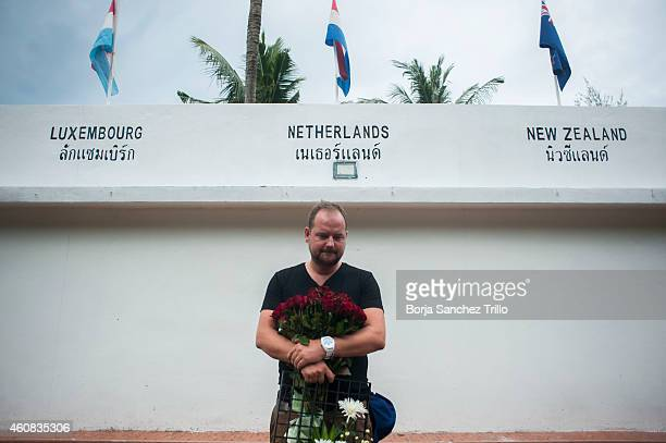 Dutch man who survived the 2004 tsunami reacts before placing flowers at the Tsunami Memorial Wall near Mai Khao Beach on December 26 2014 in Phuket...