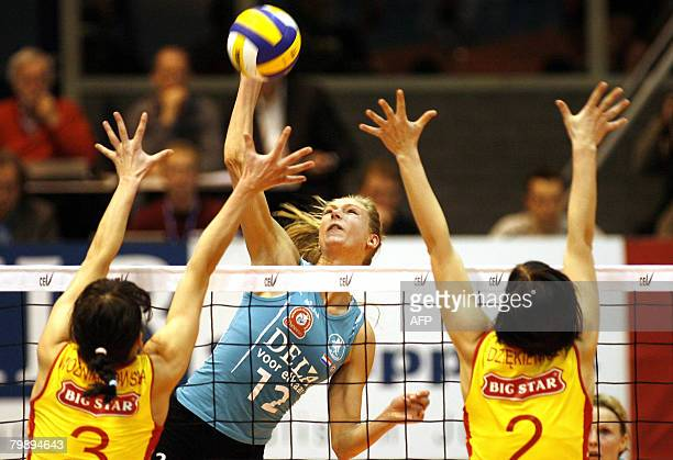 Dutch Manon Flier hits the ball past a block of Polish Anna Wozniakowska and Eleonora Dziekiewicz February 21 2008 during the Champions League match...