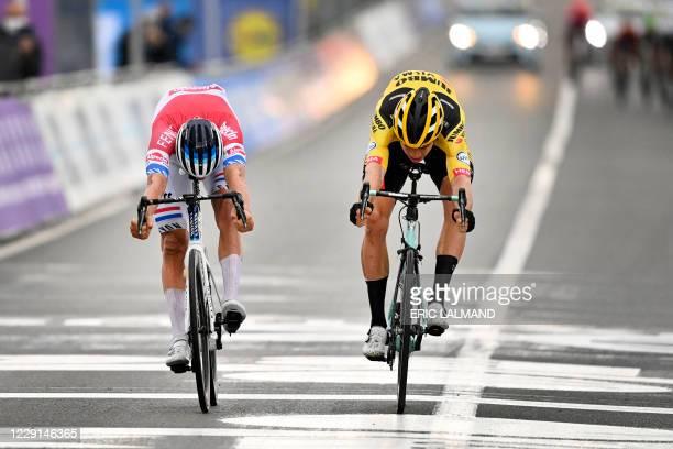 Dutch Mathieu van der Poel of Alpecin-Fenix and Belgian Wout Van Aert of Team Jumbo-Visma cross the finish line of the 'Ronde van Vlaanderen - Tour...