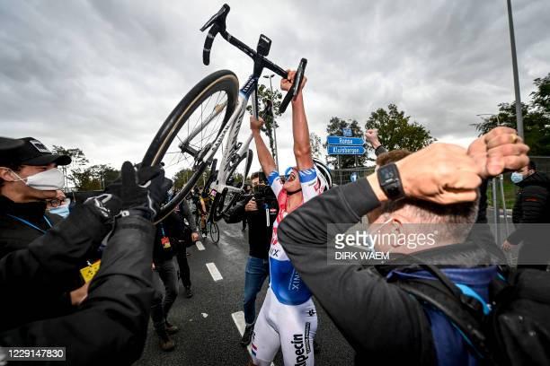 Dutch Mathieu van der Poel of Alpecin-Fenix raises his bike as he celebrates after winning the 'Ronde van Vlaanderen - Tour des Flandres - Tour of...