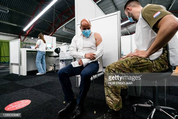Dutch Mayor of Arnhem Ahmed Marcouch is vaccinated by a serviceman at the Covid-19 vaccination site in Molenbeke, Arnhem, on May 31, 2021. - Defense...