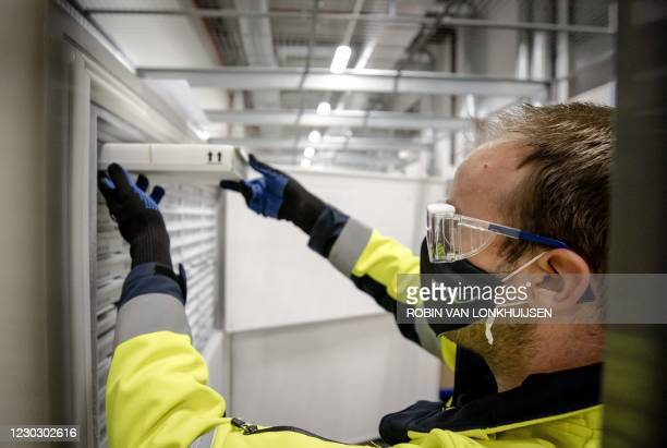 Dutch medical worker stores a box of the first shipment of doses of Pfizer-BioNTech Covid-19 vaccines, in Oss, central Netherlands, on December 26,...