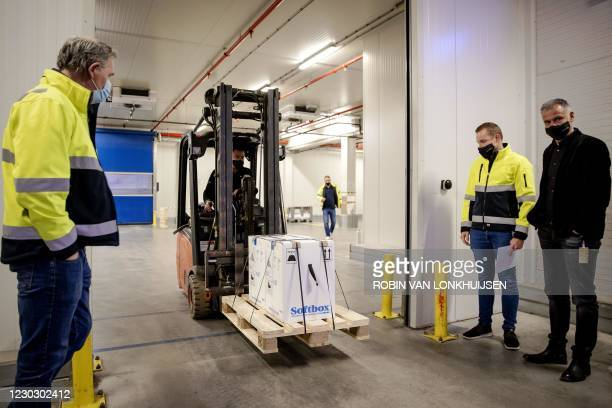 Dutch medical workers load a cart of boxes of the first shipment of doses of Pfizer-BioNTech Covid-19 vaccines, in Oss, central Netherlands, on...