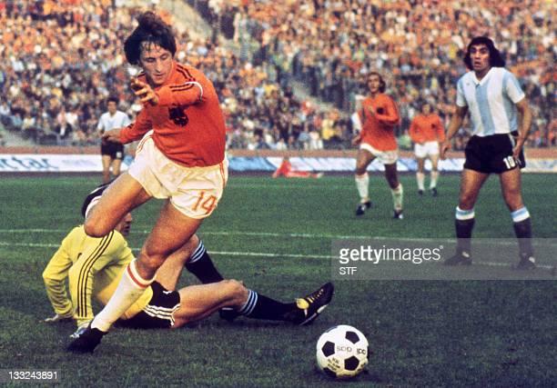 Dutch midfielder Johann Cruyff dribbles past Argentinian goalkeeper Daniel Carnevali on his way to scoring a goal during the World Cup quarterfinal...