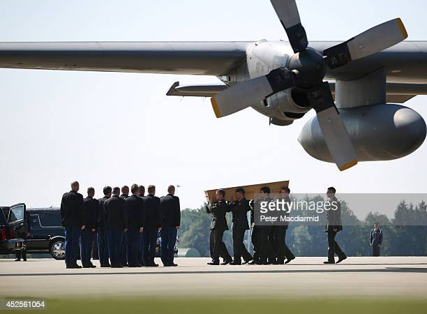 Dutch military personnel carry a coffin containing an unidentified body from the crash of Malaysia Airlines flight MH17 under the wing of a Royal...