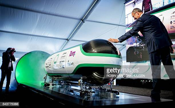 Dutch Minister for economic affairs Henk Kamp touches the prototype during the unveiling of the Hyper Loop capsule from the Delft University of...