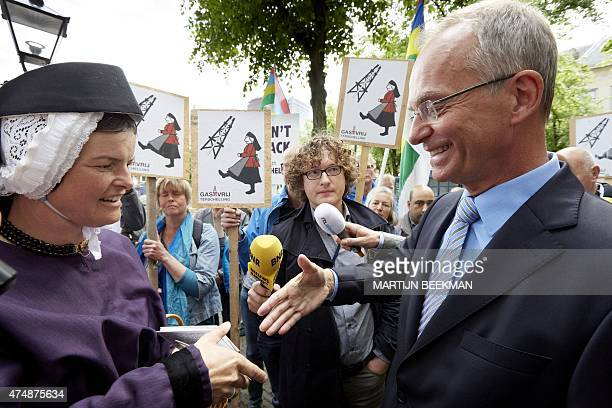 Dutch Minister of Economic Affairs Henk Kamp stands next to people protesting against gas extraction in Terschelling one of the West Frisian islands...