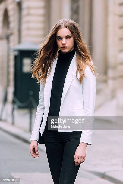 Dutch model Estella Boersma wears a buttonless white blazer over a black turtleneck and jeans after the Alberta Ferretti show on Day 1 of Couture FW...