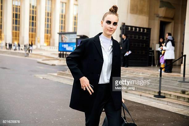 Dutch model Julia Bergshoeff exits the Sacai show at Th����tre National de Chaillot Trocadero in a top bun by Guido Palau and bold smokey black eye...