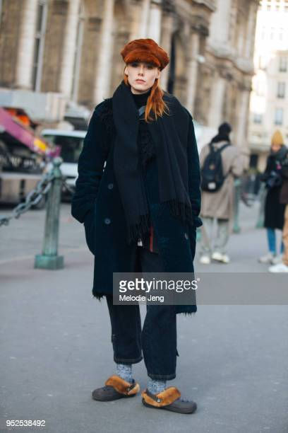 Dutch model Kiki Willems wears and orange fur newsboy cap, black peacoat, scarf, and pants, gray socks, and brown Christopher Kane fur Croc shoes on...