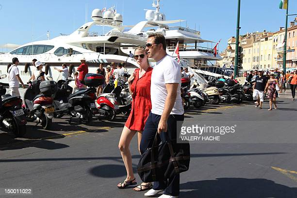 Dutch model Lara Stone walks with an unidentified person along the harbor in the French Mediterranean city of SaintTropez on August 8 2012 AFP PHOTO...