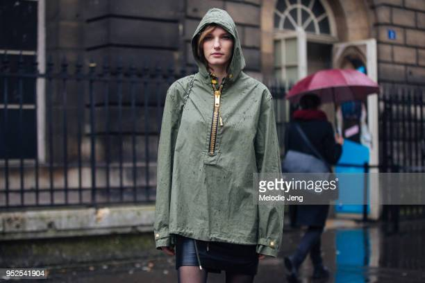 Dutch model Marique Schimmel wears Valentino Palm Angels a green hooded zip shirt and topshop leather skirt in the rain on March 04 2018 in Paris...