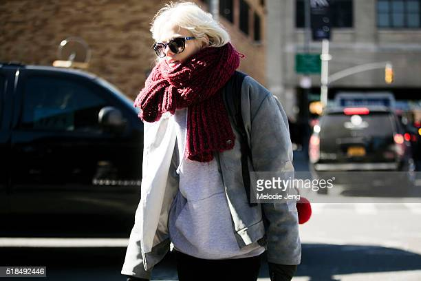 Dutch model Marjan Jonkman exits the Derek Lam show at Skylight Clarkson North in a gray jacket white hoodie and a large red knit scarf during New...