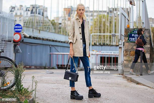 Dutch model Marjan Jonkman wears a tan trench coat cropped jeans a black Dior purse and platform brogues after the Loewe show at Maison de l'Unesco...