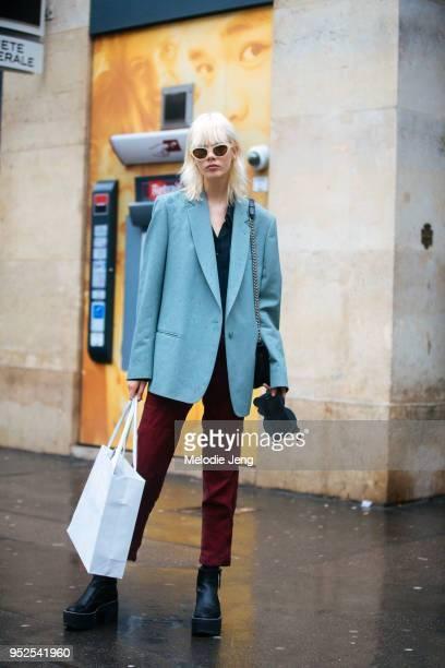 Dutch model Marjan Jonkman wears white sunglasses a teal blazer dark red pants and platform black boots on March 04 2018 in Paris France