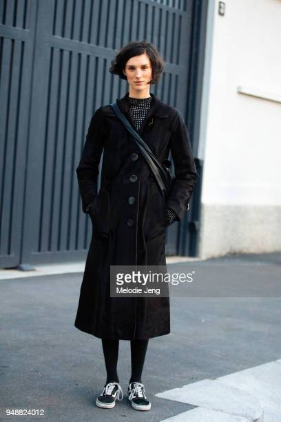 Dutch model Marte Mei Van Haaster wears a long black coat with buttons and black Vans sneakers during Milan Fashion Week Fall/Winter 2018/19 on...