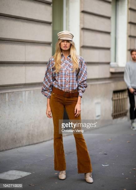 Dutch model Romee Strijd wearing flat cap checked button shirt brown flared pants boots is seen during Paris Fashion Week Womenswear Spring/Summer...