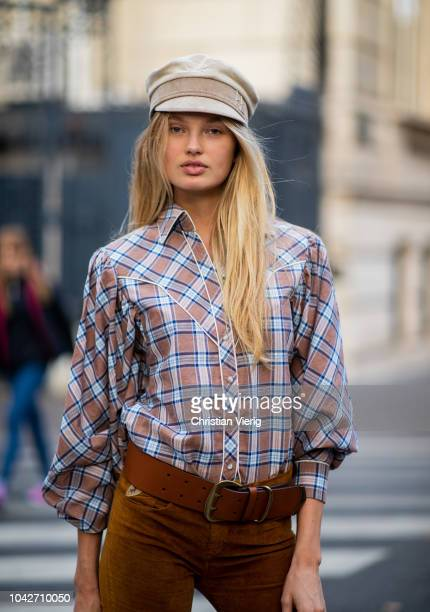Dutch model Romee Strijd wearing flat cap checked button shirt brown flared pants boots is seen during Paris Fashion Week Womenswear Spring/Summer...