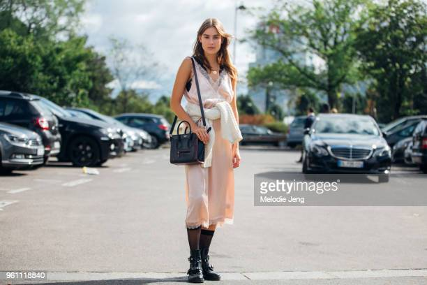 Dutch model Vera Van Erp wears a pink slip dress with a white knit sweater tied around her waist black socks black Balenciaga buckle boots and a...