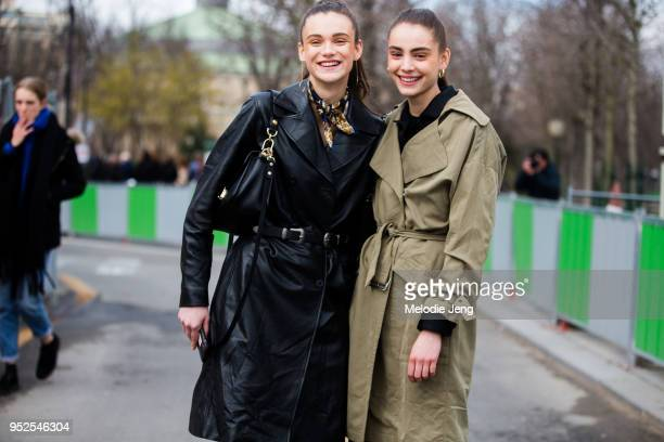 Dutch models Sara Dijkink Romy Schonberger wear black and green belted trench coats and gold earrings after the Chanel show on March 06 2018 in Paris...