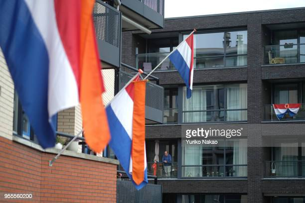 Dutch national flags are outside houses as a man looks out from his balcony to celebrate the Koningsdag or the King's day April 27 in Katwijk,...