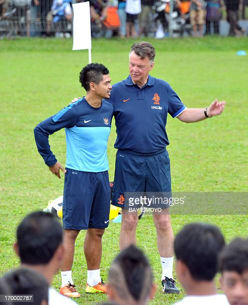 Dutch national football team coach Louis Van Gaal talks to Indonesia national football team captain Bambang Pamungkas during a coaching clinic for...