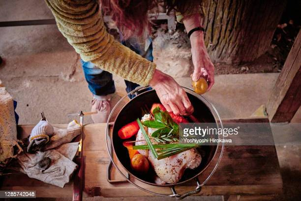 dutch oven cooking in a wooden camp hut - ダッチオーブン ストックフォトと画像