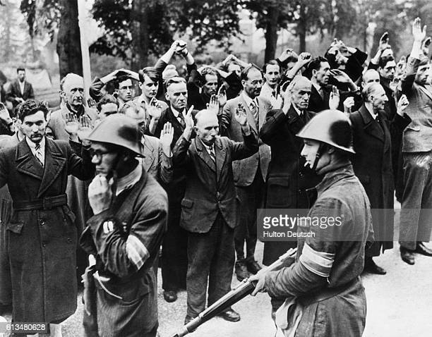 Dutch patriots, wearing orange arm-bands, herd people accused of collaborating with Nazis occupiers of their town of Nijmegen, after the town was...