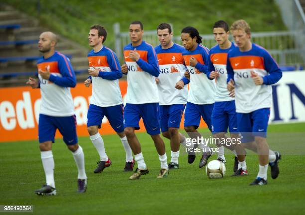Dutch players Wout Brama Peter Wisgerhof and Urby Emanuelson jog during a training a session of the Dutch national team in Katwijk on October 4 2010...