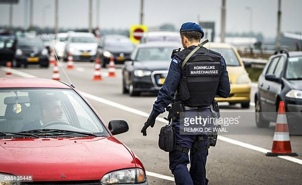 A Dutch police officer patrols among cars on the high way to Schipol Airport in Amsterdam on August 2 2016 as security was stepped up in and around...