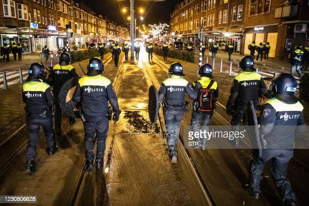 Dutch police officers patrol in the streets of Rotterdam, during the curfew time, on January 26 a day after police clashed with groups of...